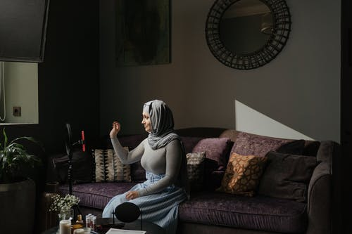 Woman in Gray Hijab Sitting on Brown Couch