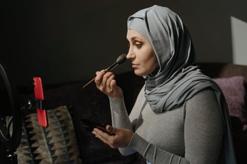 Woman in Gray Hijab Holding Black Brush