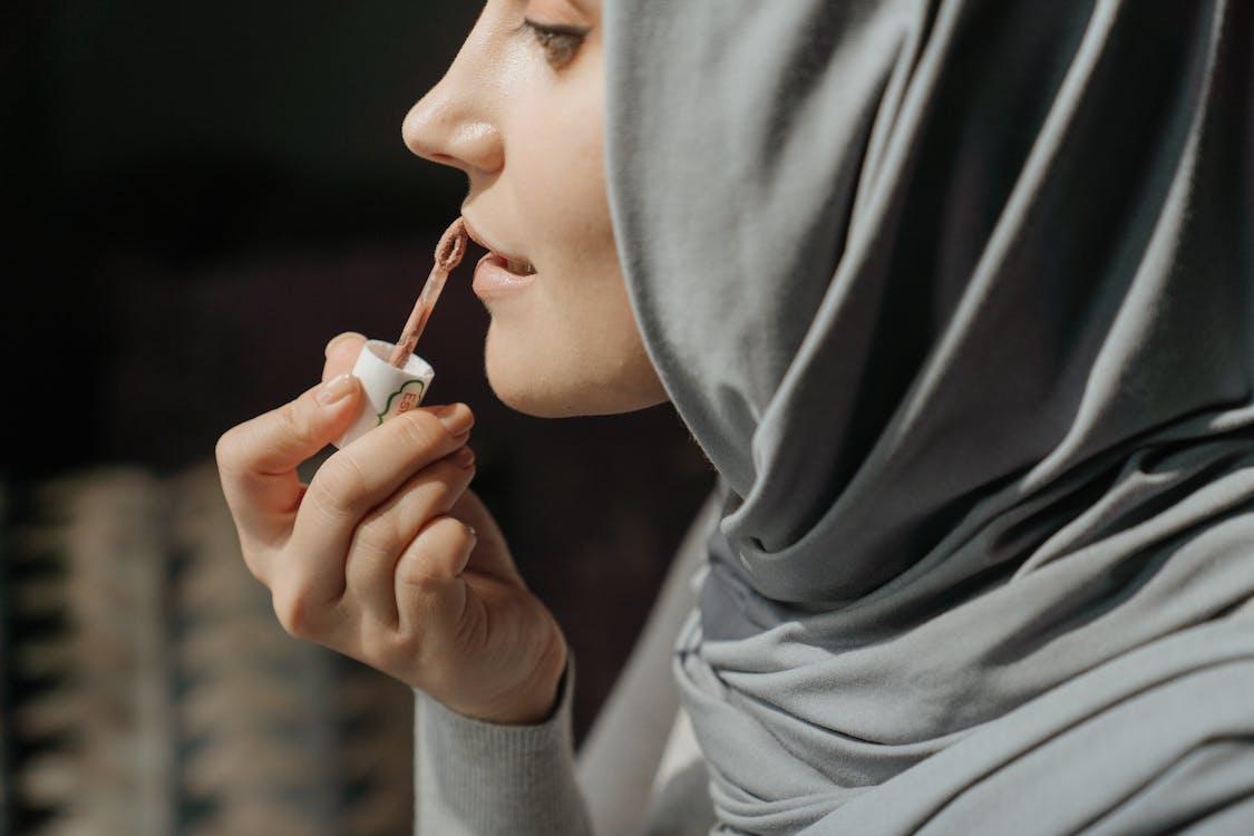Wanita Berjilbab Abu Abu Memegang Lipstik
