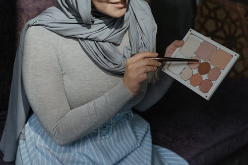 Woman in Gray Long Sleeve Shirt and Gray Hijab Holding White Tablet Computer