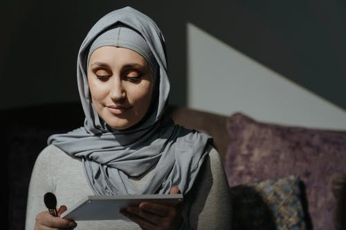 Woman in Gray Hijab Holding White Tablet Computer