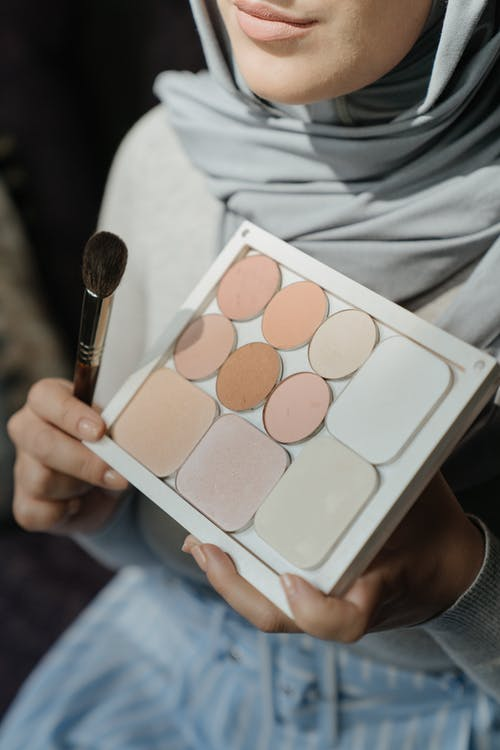 Person Holding Makeup Brush and Makeup Palette