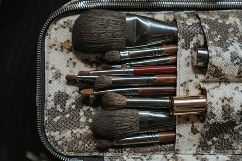 Makeup Brushes on Brown and White Textile