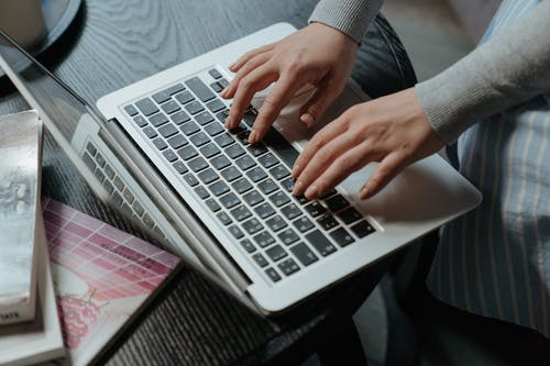 Person in Gray Sweater Using Macbook Pro