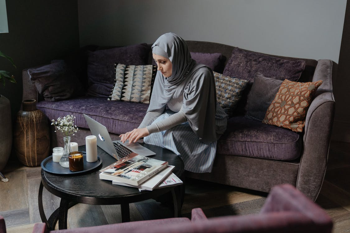 Woman in Gray Hijab Sitting on Couch
