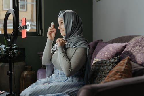 Woman in Gray Hijab Sitting on Bed