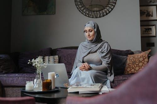 Vrouw In Grijze Hijab Zittend Op De Bank