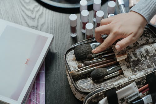 Person Holding White and Brown Makeup Brush Set
