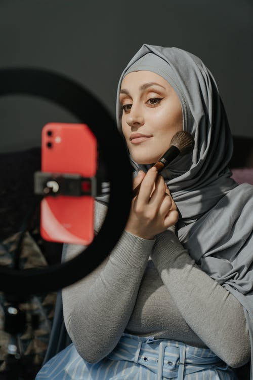 Woman in Gray Hijab Holding Red Smartphone