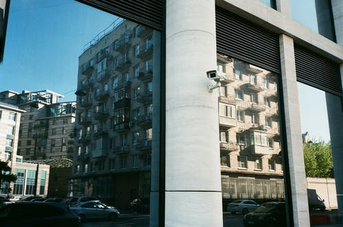 Tall beige multi storey dwelling house reflecting in window of modern construction with small security camera mounted on thick white column