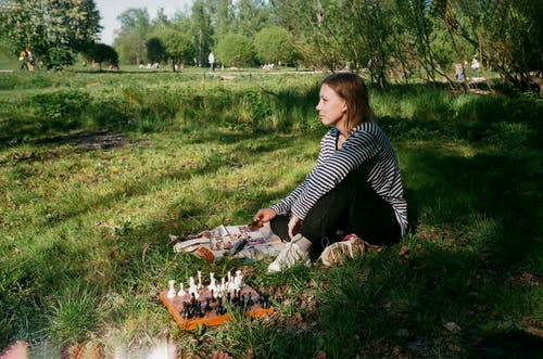 Full body side view of thoughtful young slender female in casual clothing looking ahead while playing chess in park immersed in greenery in sunlight