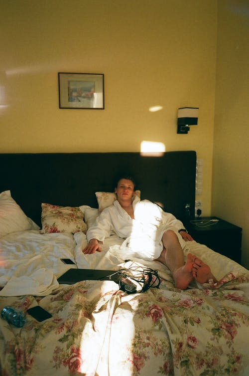 Pensive man resting on bed in dark room