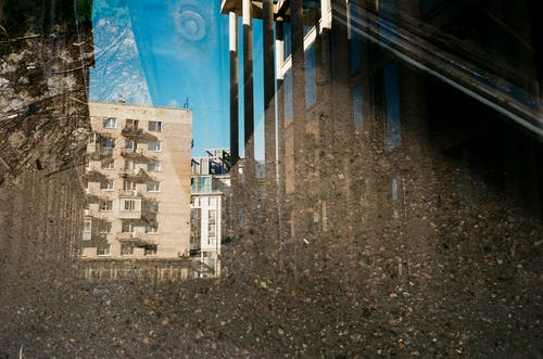 Through glass of old multi storey construction reflecting from ground covered with water in daylight