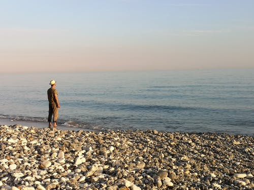 Photo Of Man Standing On Seashore
