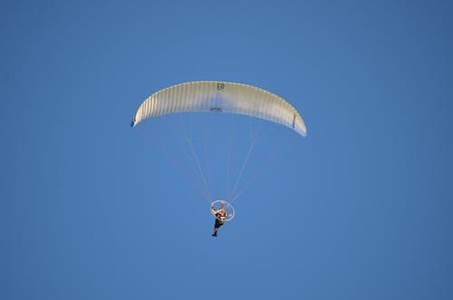 Person in Blue Shirt Riding Parachute