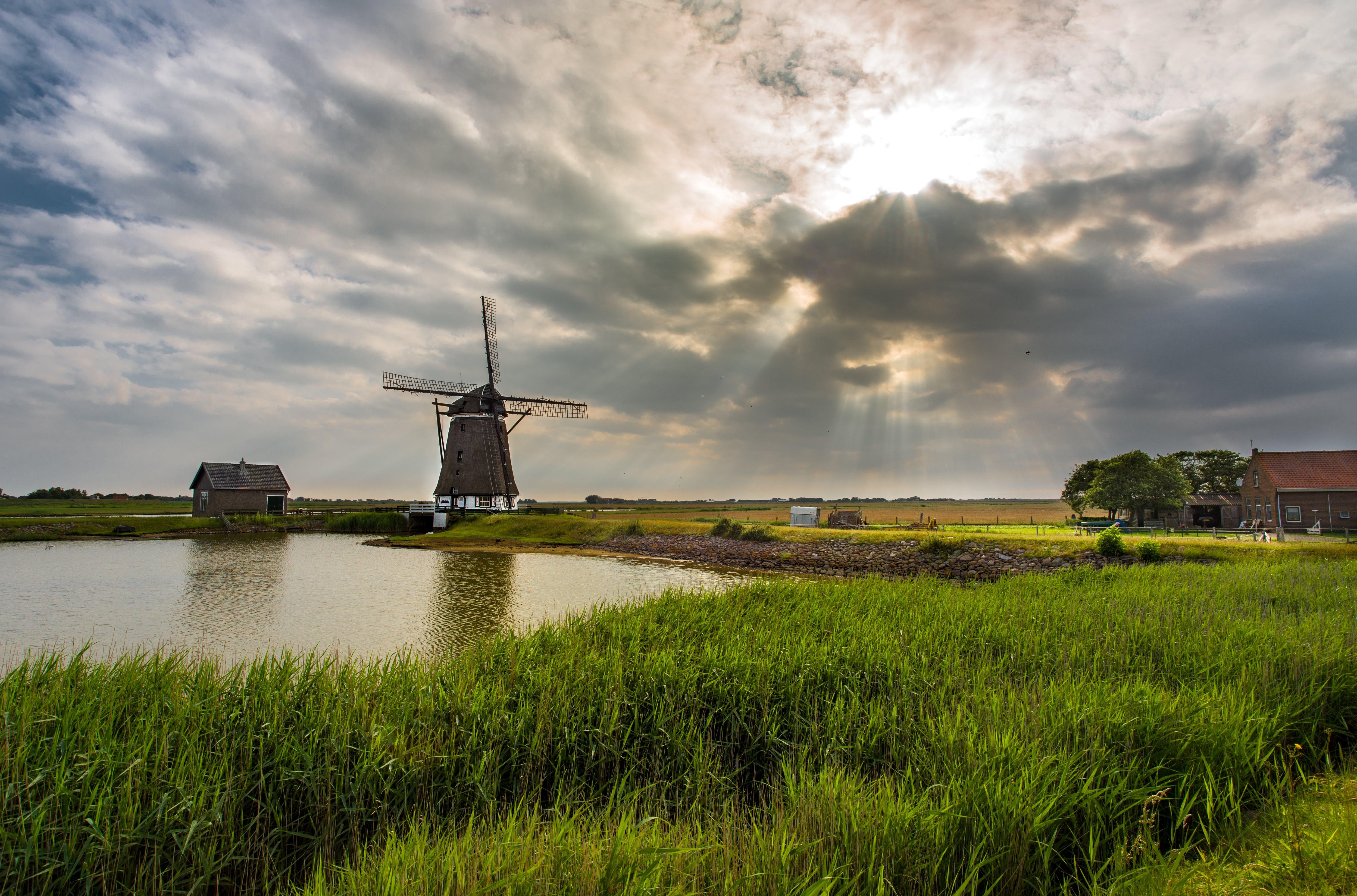 Gray Windmill Near Body of Water
