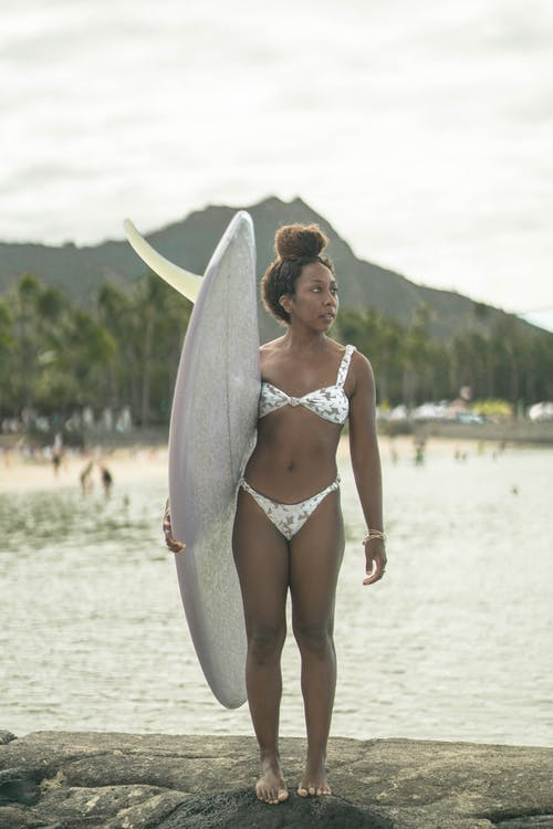 Photo Of Woman Carrying A Surfboard