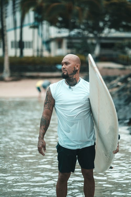 Photo Of Guy Carrying Surfboard