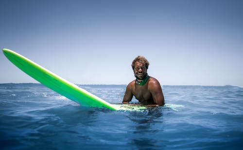 Photo Of Man Riding Surfboard