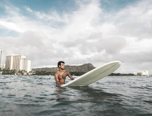 Photo Of Man Riding A Surfboard