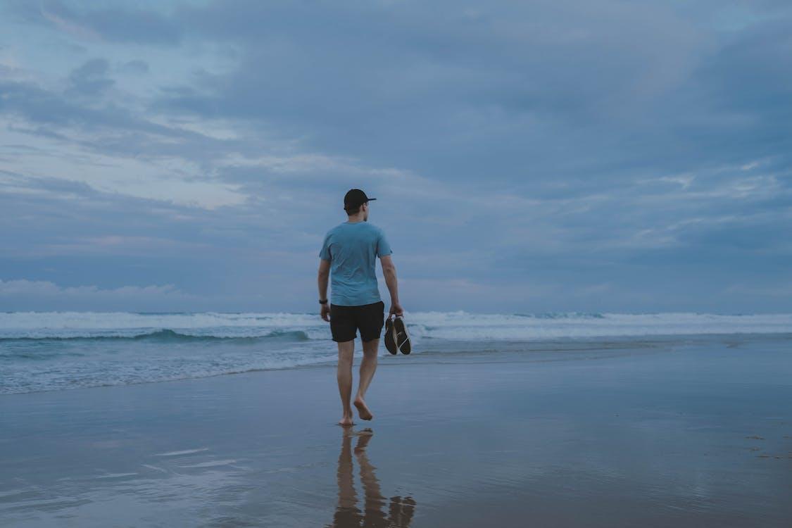 Photo Of Man Walking On Seashore