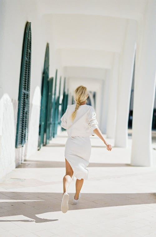 Женщина в белом платье с длинным рукавом идет по коридору