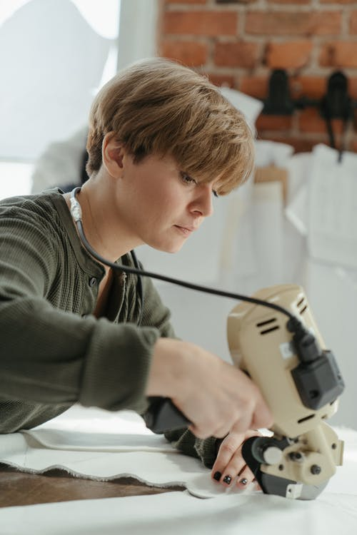 Boy in Green Sweater Holding Black and White Power Tool
