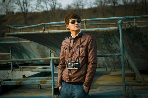 Man Wearing Brown Leather Jacket With Black Dslr Camera Standing on Skate Park Selective-focus Photography