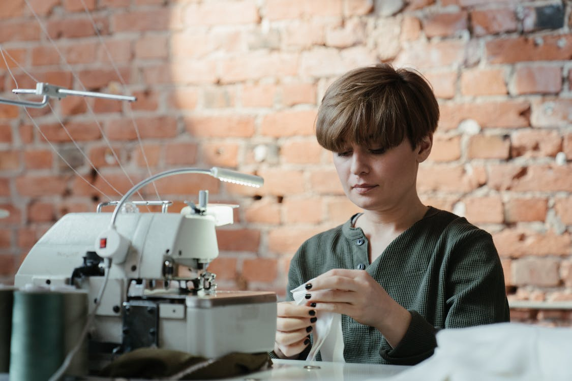 Man in Green and Black Stripe Sweater Using White and Gray Sewing Machine