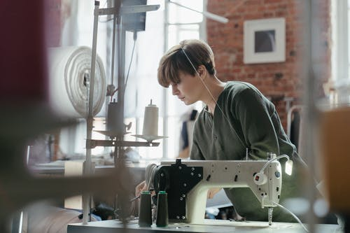 Woman in Green and Brown Camouflage Shirt Using Sewing Machine