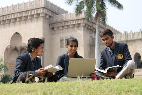 Indian students doing homework in campus meadow