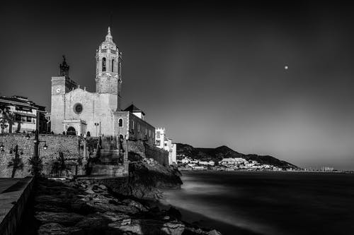 Black and white of Maricel Museum on rocky coast of silent sea under dark sky at night in Sitges in Spain