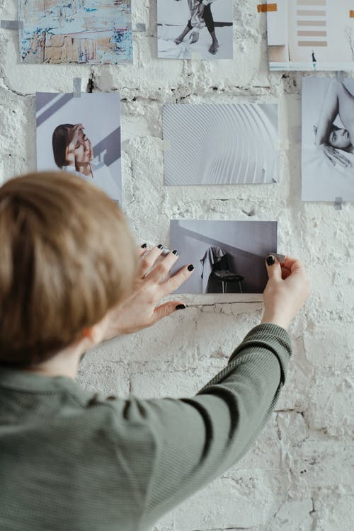 Woman in Gray Sweater Holding White Printer Paper