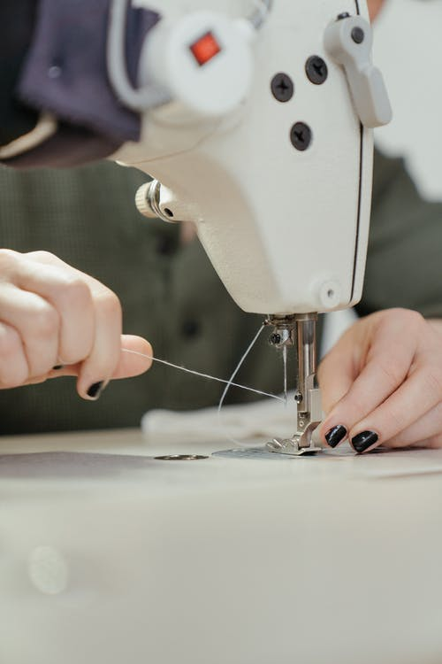 Person Sewing White Sewing Machine