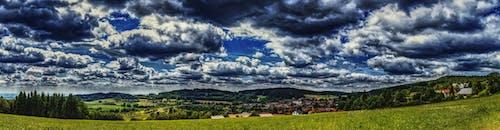 Green Grass Field Under Cloudy Skies