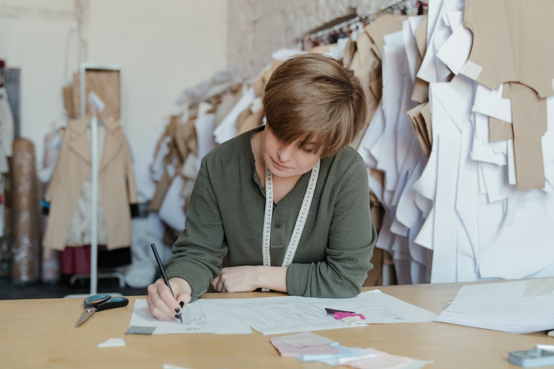 Woman in Gray Cardigan Writing on White Paper