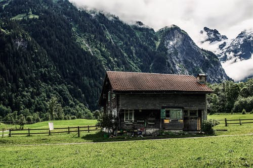 Old wooden house located in green valley near mountains