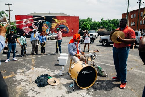 Group of anonymous African American people in casual clothes playing musical instruments on street near audience
