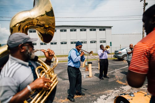 Happy black men playing music together on sunny day