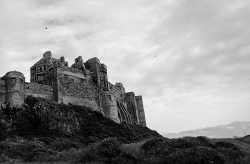 Grayscale Photo of Bamburgh Castle