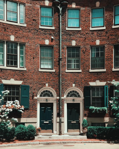 Brown Brick Building With White Flowers