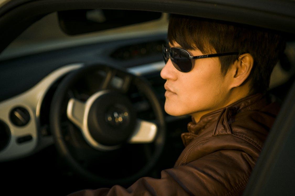 Man Wearing Sunglasses Sitting on Driver's Seat