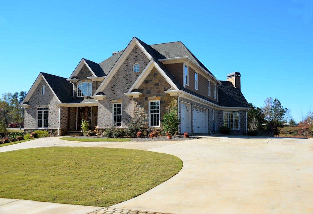 Brown Concrete House Near Grass Field