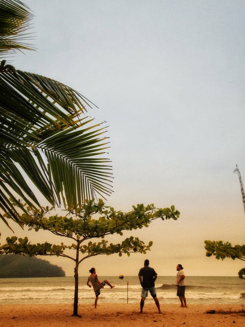 People having fun together on tropical sandy beach near waving ocean while playing football