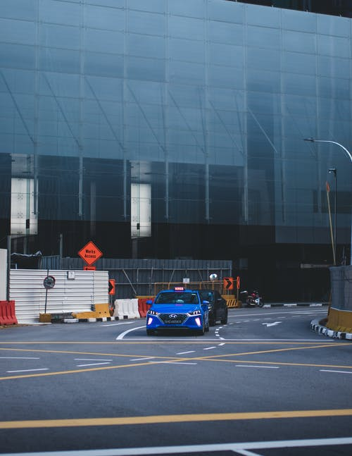 Colorful cars driving on asphalt roadway near glass facades of building on busy day