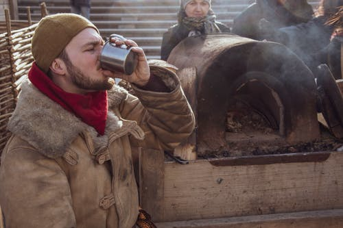 Man in Brown Coat Drinking from Cup