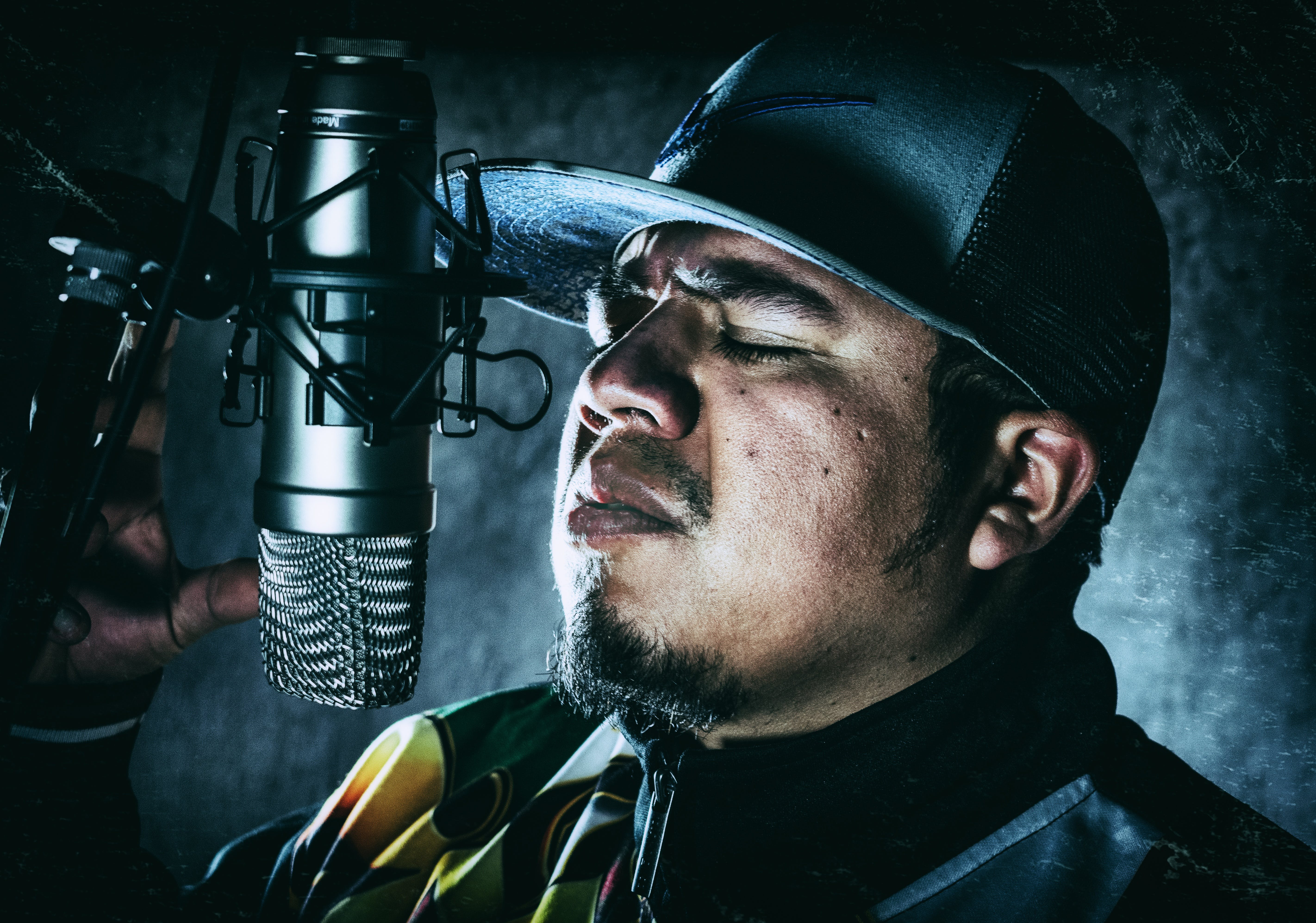 Man in Black Flat-brimmed Hat in Front of Condenser Microphone