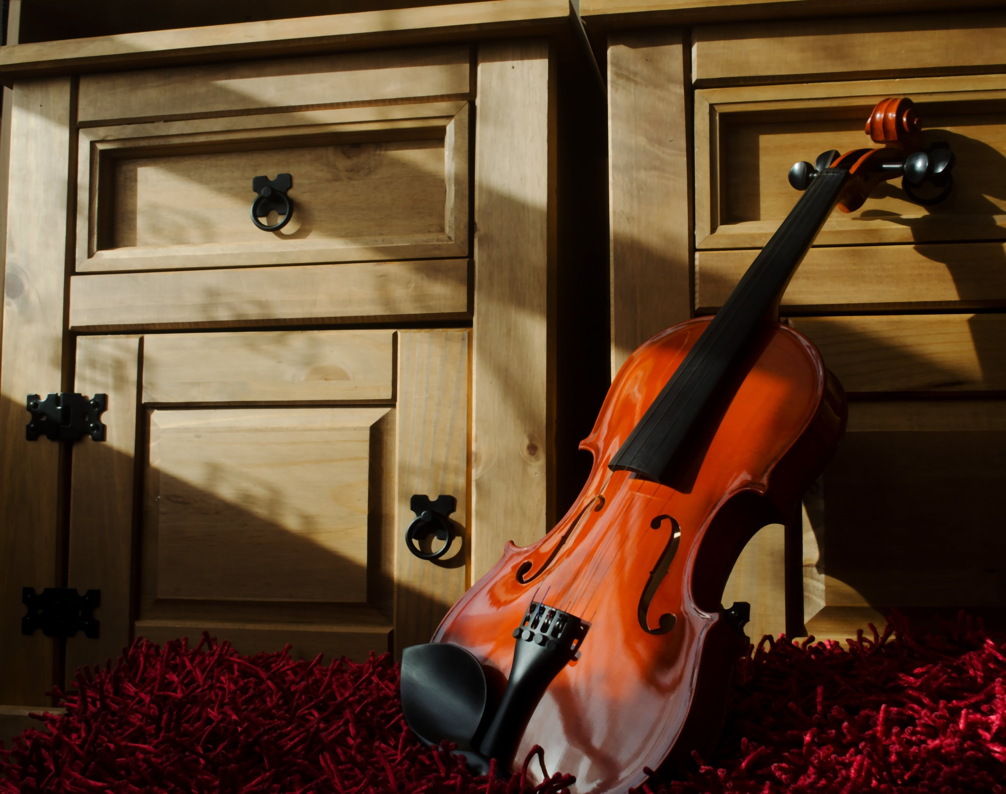 Brown Violin Leaning on Brown Wooden Cabinet