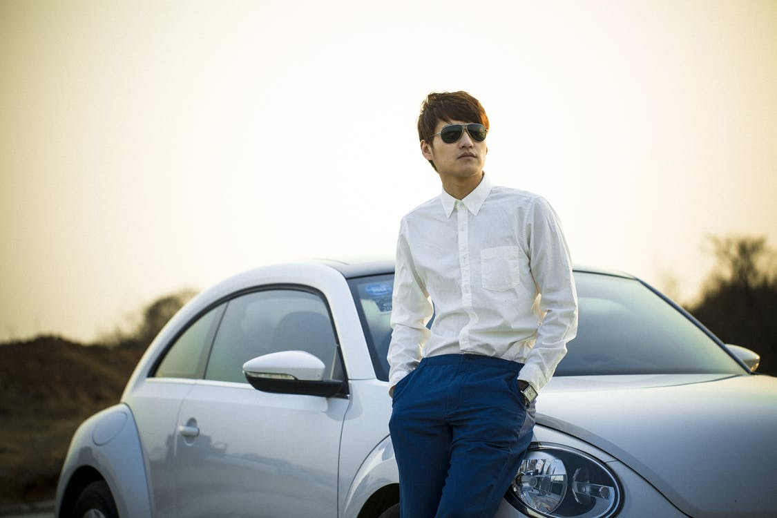 Man in White Button Down Shirt Leaning on Silver Beetle Car