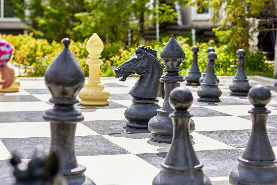 Big checkered board with chess pieces in garden